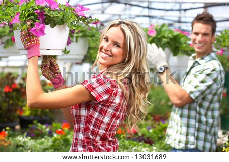 Young smiling people florists working in the garden