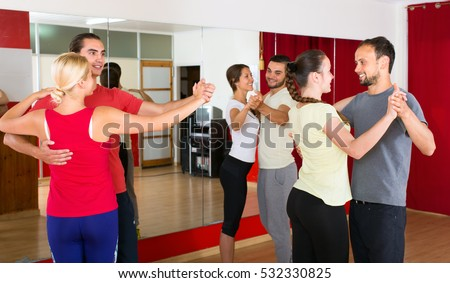 Young smiling people learning to dance waltz in pairs in dancing studio