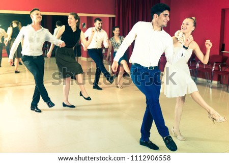 Young smiling people practicing vigorous jive movements in dance class #1112906558