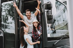 Young Smiling People Traveling on Tourist Bus. Group of Happy Friends Standing Together in Doors of Tour Bus. Traveling, Tourism and People Concept. Happy Travelers on Trip. Summer Vacation