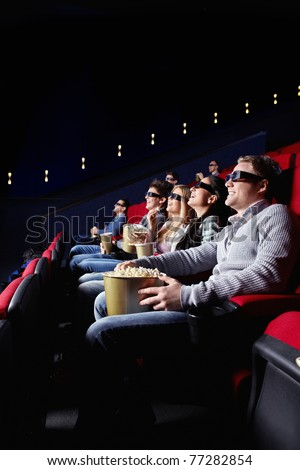 Young smiling people watch movies in cinema - stock photo