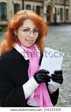 Young smiling red haired lady wearing glasses holding a book. The girl looks like a teacher or a student.