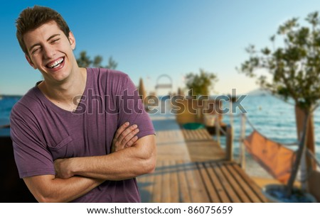 Young smiling relaxed man at the beach in a summer day