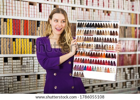 Young smiling saleswoman helping to choose new hair dye for coloring in specialized store