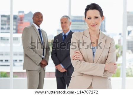 Young smiling secretary crossing her arms in front of two executives