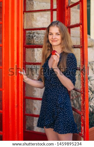 Young smiling seducing woman eating strawberry in hand in red telephone cabin #1459895234