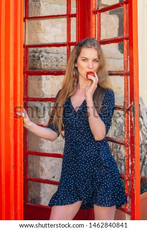 Young smiling seducing woman eating strawberry in hand in red telephone cabin #1462840841