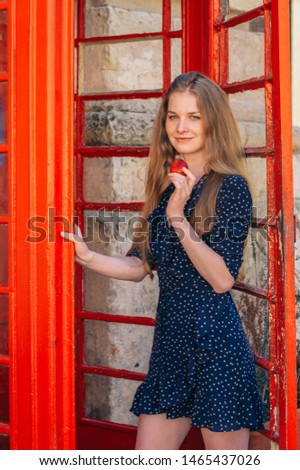 Young smiling seducing woman eating strawberry in hand in red telephone cabin #1465437026