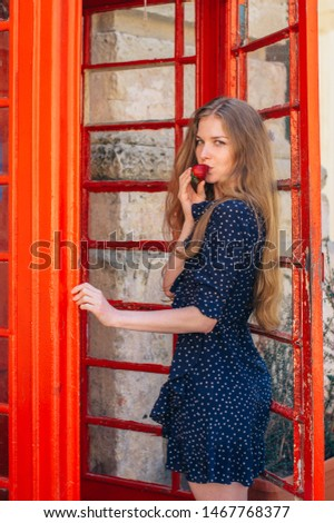 Young smiling seducing woman eating strawberry in hand in red telephone cabin #1467768377