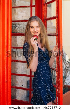 Young smiling seducing woman with strawberry in hand in red telephone cabin #1467916712