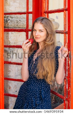 Young smiling seducing woman with strawberry in hand in red telephone cabin #1469395934