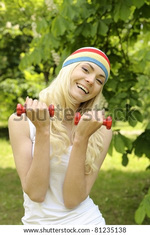 Young smiling sporty woman is working out outdoor.