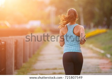 Young smiling sporty woman running in park in the morning. Fitness girl jogging in park. Rear view of sporty girl running on embankment #721807549
