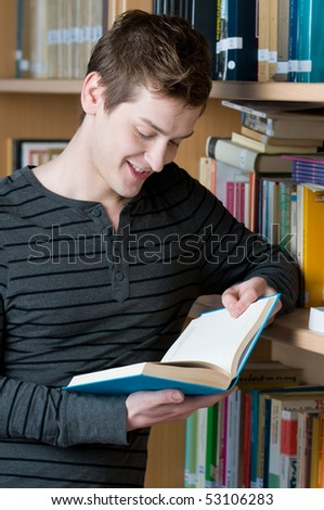 Young smiling student reading a book in a library