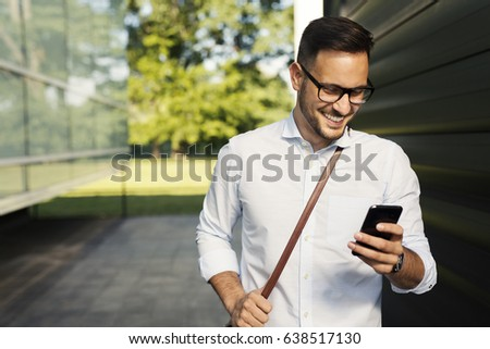 Young smiling student with glasses using smart phone #638517130
