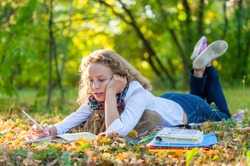 Young smiling student woman writing and reading book in park, preparing for exams at university or college. Education concept, copy space