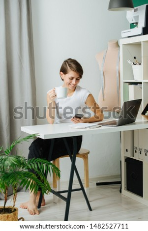 Young smiling tired tailor woman sitting at her workplace, behind the desk with cup of coffee and texting on her phone during coffee break at office. She has short brown hair, casually dressed.