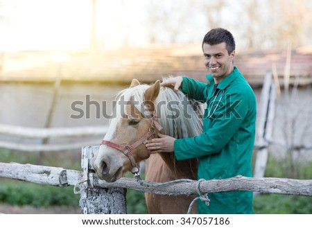 Young smiling veterinarian cuddling horse on the ranch