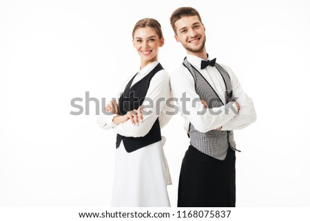 Young smiling waiter and waitress in white shirts and vests sstanding back to back joyfully looking in camera with arms folded over white background