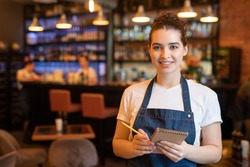 Young smiling waitress in workwear standing in front of camera in luxurious restaurant and going to writie down order of client