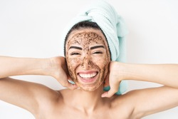 Young smiling woman applying coffee scrub mask on face - Happy girl having skin care spa day at home - Healthy alternative natural exfoliation treatment and people lifestyle concept