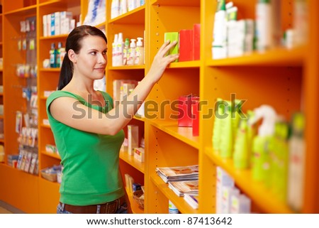 Young smiling woman buying medicine in a pharmacy