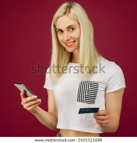 Young smiling woman buys online. Holds a smartphone and a credit card in hand on ruby background
