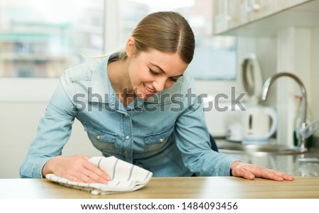 Young smiling woman cleaning kitchen surfaces at home