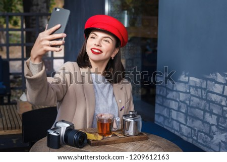 Young smiling woman drinking tea in a cafe and making selfie #1209612163