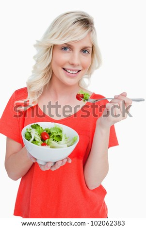 Young smiling woman eating a fresh salad with a fork against a white background