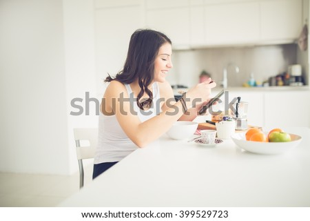 Young smiling woman eating healthy breakfast and smiling.Starting your day.Dieting,fitness and well being.Positive energy emotion.Productivity,happiness,enjoyment concept.Morning ritual.Technology