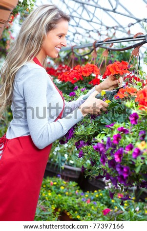 Young smiling woman florist working in the greenhouse.