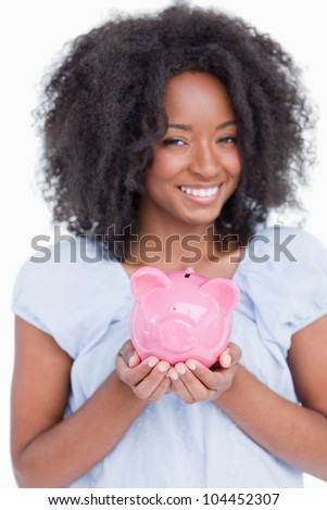 Young smiling woman holding a piggy bank against a white background
