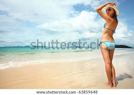 Young smiling woman holding a straw hat and looking to somewhere #63859648