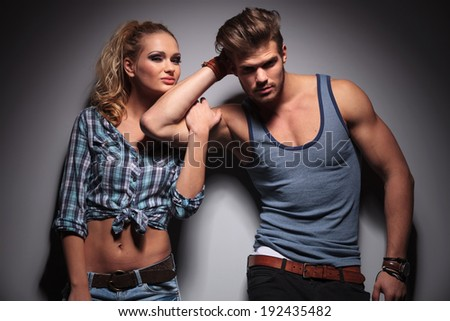 young smiling woman holding her boyfriend by his biceps, studio shot