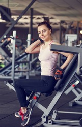 Young smiling woman in a fitness center. Happy beautiful girl in a gym