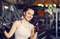 Young smiling woman in a fitness center. Happy beautiful girl in a gym showing thumbs up