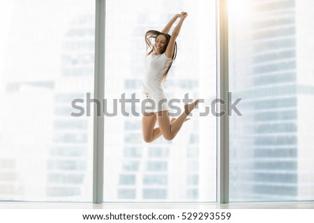 Young smiling woman in a modern room jumping high for joy, passed her exams, bought a new flat, met a new boyfriend, being proposed, hired for a good job, graduated with honor, parents left home