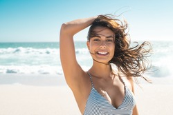 Young smiling woman in bikini at tropical beach looking at camera. Portrait of beautiful latin girl in swimwear with ocean in background. Happy tanned hispanic woman relaxing at sea and copy space.