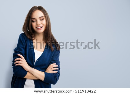 Young smiling woman in casual blue clothing with crossed arms, with copyspace area for advertise text or slogan. Caucasian brunette model in emoshions and optimistic, positive, happy feeling concept.  #511913422
