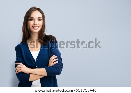 Young smiling woman in casual blue clothing with crossed arms, with copyspace area for advertise text or slogan. Caucasian brunette model in emoshions and optimistic, positive, happy feeling concept.
