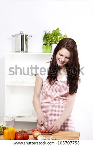 young smiling woman in kitchen cutting tomatoes