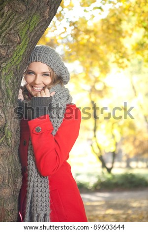 young smiling woman in season warm clothing in autumn park