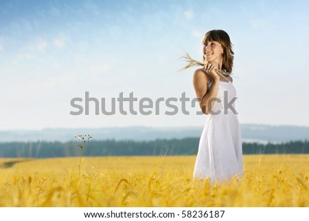 Young smiling woman in white dress standing in yellow wheat field