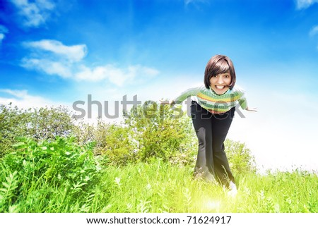 Young smiling woman into the field against the blue sky