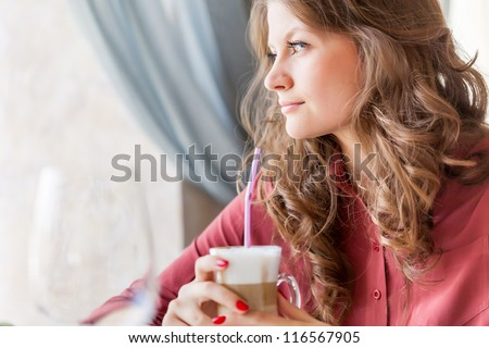 Young smiling woman is drinking coffee in a cafe and holding a tablet computer in hands