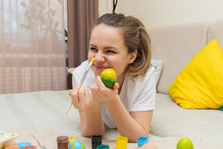 Young smiling woman lays on bed and decorating Easter Egg in yellow color. Inner people lifestyle before Easter Holliday.