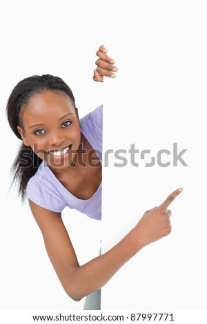 Young smiling woman looking around the corner pointing at something on white background