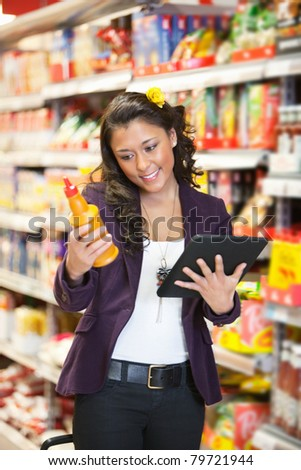 Young smiling woman looking at a product while holding digital tablet in shopping centre