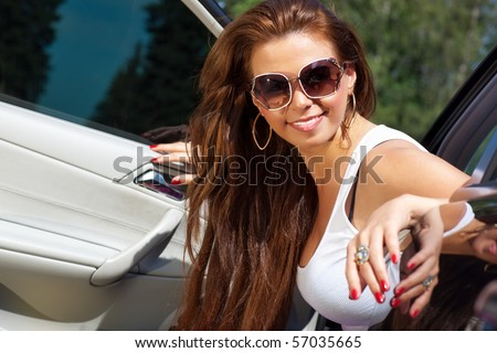 Young smiling woman looking out of her car.